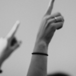 black and white photo of hands raised in the air for generation eqaulity